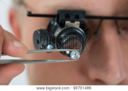 Person Looking At Diamond With Magnifying Loupe