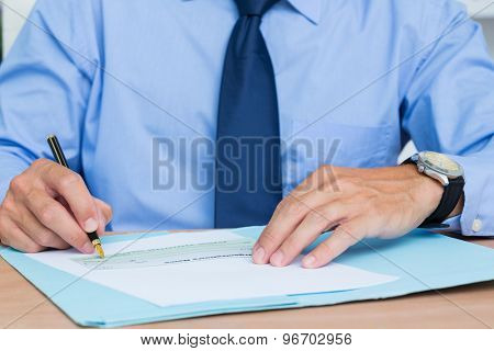 Businessman writing a contrat before signing it in the office