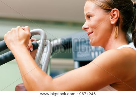 Woman in gym on machine exercising
