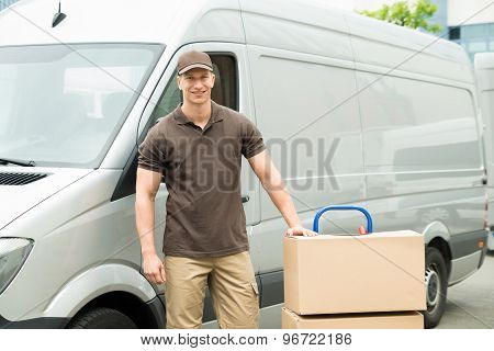 Delivery Man With Cardboard Boxes On Trolley