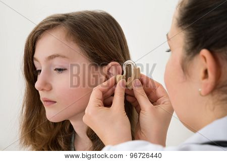 Close-up Of Doctor Inserting Hearing Aid In The Ear Of A Girl poster