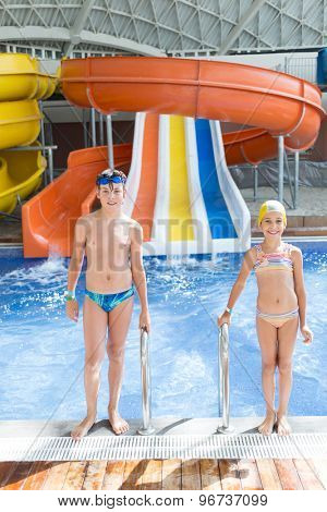 brother and sister in the pool with water slides
