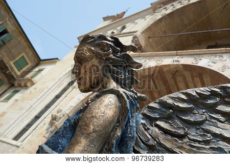VERONA, ITALY - JULY 13: Bronze statue The Blue Angel of Acceptance, or Hospitality, by Albano Poli, in front of Duomo di Verona Cathedral. July 13, 2015 in Verona.