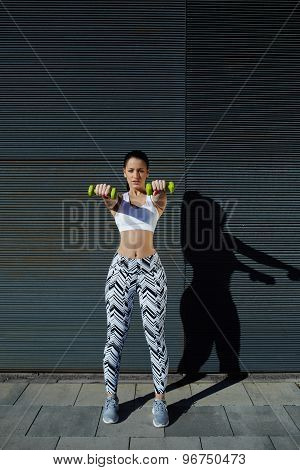 Athletic woman holding weights with hands up at her front getting arms in great shape