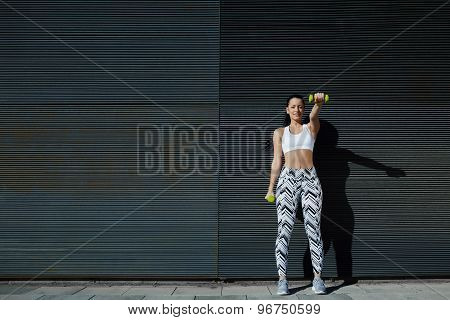 Athletic young woman lifting weights standing with arms tense against black wall outdoors