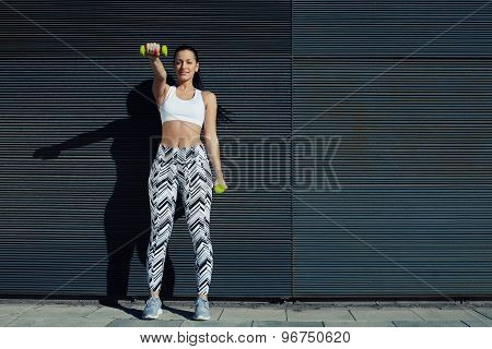 Sporty young woman lifting weights standing with arms tense against black wall outdoors
