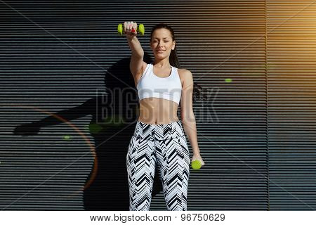 Charming woman lifting weights standing with arms tense against black wall background at sunset
