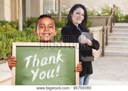 Happy Hispanic Boy Holding Thank You Chalk Board Outside on School Campus as Teacher Looks On.