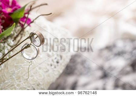 Close Up Of Two Wedding Rings Hanging On Twigs Of Bridal Bouquet With Fuchsia Colored Flowers