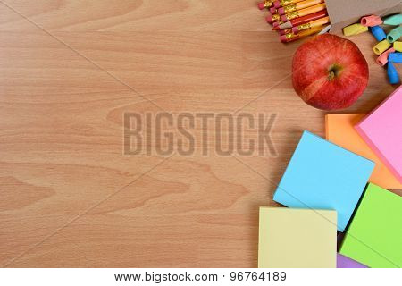 High angle back to school still life on top of a wood teachers desk. An apple, note pads, pencils and erasers with copy space.