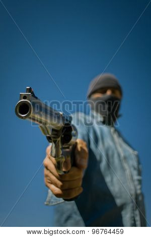 Hooded man with 44 magnum handgun threatening