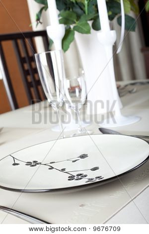 A dinner plate, knife, spoon and fork