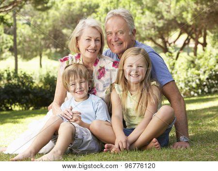 Grandparents And Grandchildren Sitting In Park Together