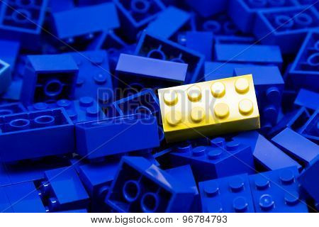 Pile of blue color building blocks with selective focus and highlight on one particular yellow block