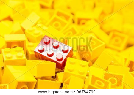 Pile of yellow color building blocks with selective focus and highlight on one particular red block