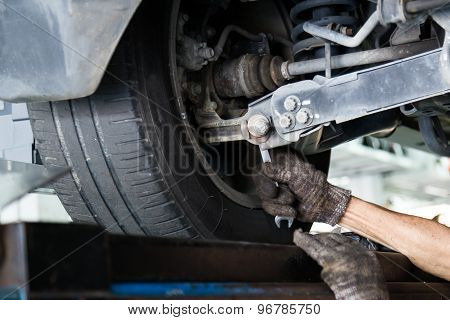 Mechanic adjusting the bolt on the wheels during wheel alignment exercise