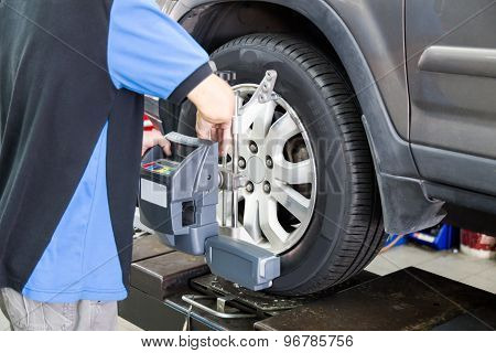 Mechanic fixing the wheel alignment device onto a car wheel. Focus is on the car wheel and wheel ali