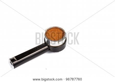Coffee portafilter filled with finely grounded coffee in white background