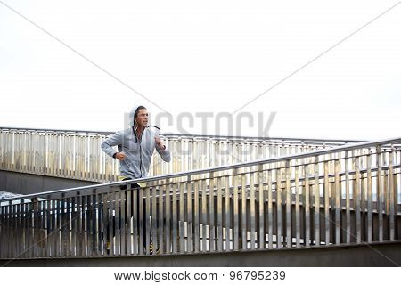 Male jogger exercising at early morning  while listening to music with headphones