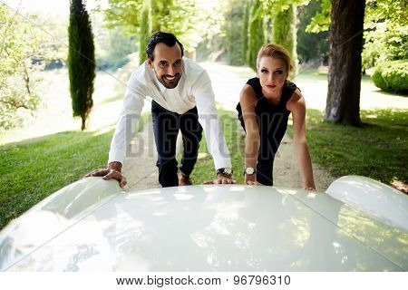 Attractive young couple of travelers faced with the problem their luxurious new white car broken