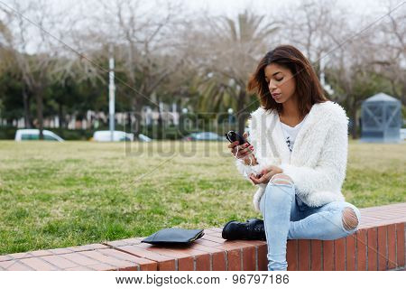 Portrait of young stylish hipster girl holding smart phone while sitting in the park outdoors