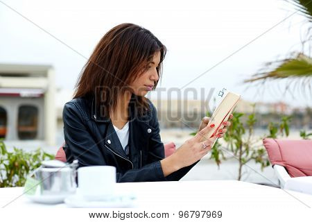 Charming young afro american woman reading novel or book during her recreation time at weekend