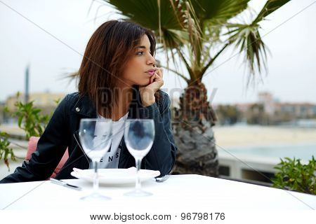 Charming female hipster sitting on the terrace of sidewalk cafe with palm tree on background