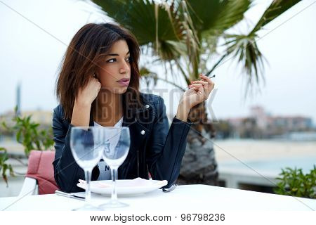 Attractive afro american woman smoking cigarette while sitting at sidewalk cafe looking pensive
