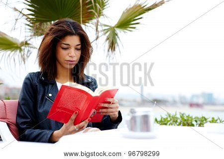 Young female hipster fascinating read book in open air coffee shop during her recreation time