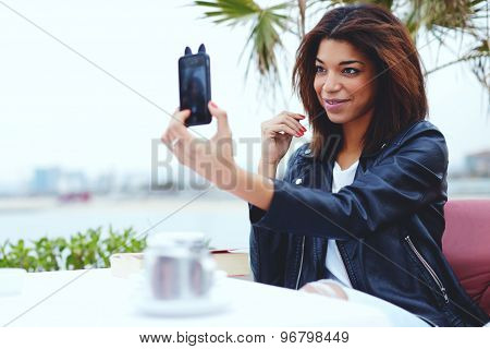 Female taking a picture of herself on smartphone while sitting in coffee shop at her recreation time