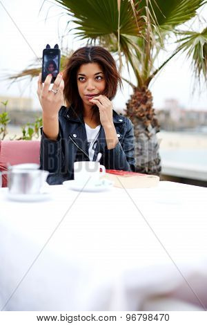 Afro american female taking fun self portrait with smartphone camera while sitting at cafe terrace