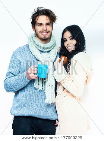 lovely cute smiling happy couple holding colorful cups. Bearded caucasian man with moustache in knitted blue sweater and scarf with brunette pretty girl in beige robe drink coffee isolated on white
