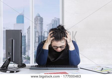 Picture of fat woman feeling dizzy with financial crisis while holding her head at office