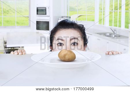 Picture of fat woman peeping boiled potato on a plate at home