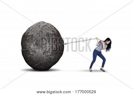 Young female entrepreneur is pulling big stone with a chain isolated on white background