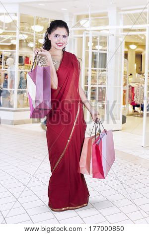 Portrait of gorgeous Indian woman wearing a red saree clothes at the mall while holding shopping bags