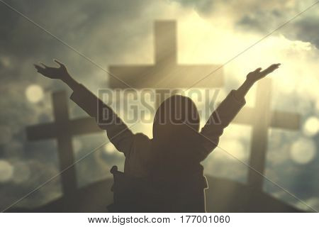 Image of handicapped woman raising hands while praying to God with three crucifixes in the hill