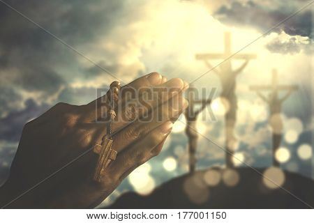 Image of human hands worshipping to the GOD while holding a rosary with crucifix symbol on the background
