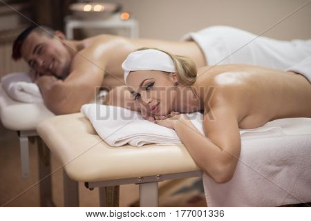 Portrait of relaxed beautiful young couple lying on massage table at spa center