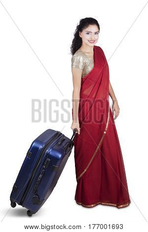 Full length of beautiful Indian woman wearing a red saree and pulling a suitcase in the studio isolated on white background