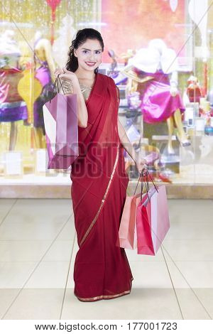 Young Indian woman standing in the shopping center while wearing a red saree clothes and holding shopping bags