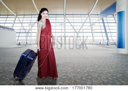 Beautiful Indian woman wearing a red saree and walking in the airport terminal while carrying a suitcase