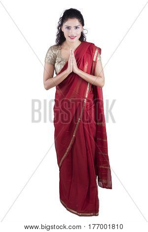 Portrait of a young Indian woman wearing a red saree clothes and showing a welcome gestures isolated on white background