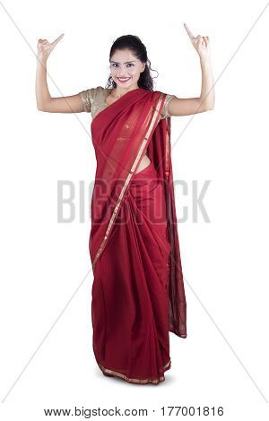 Happy Indian woman dancing in the studio while wearing a red saree clothes isolated on white background