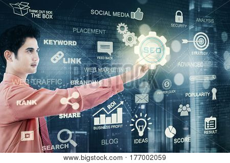 Photo of a young male manager pressing a virtual SEO icon on the futuristic screen. SEO concept