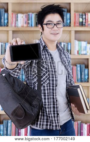 Portrait of a clever male student showing blank screen of a mobile phone while standing with bookcase in the library