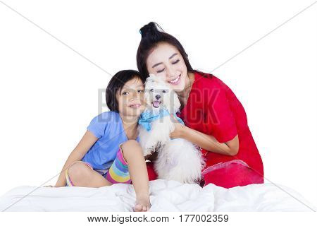 Image of young Asian mother and her child embracing a Maltese puppy while sitting in the studio isolated on white background