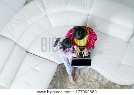 High angle view of a young mother with her daughter using a laptop while sitting on the couch