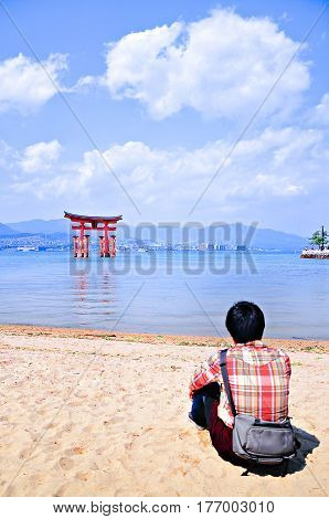 Young man enjoying the view of the floating Torii Gate Hiroshima Japan