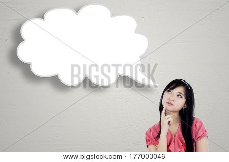 Picture of a pretty young woman thinking idea while looking at empty speech bubble